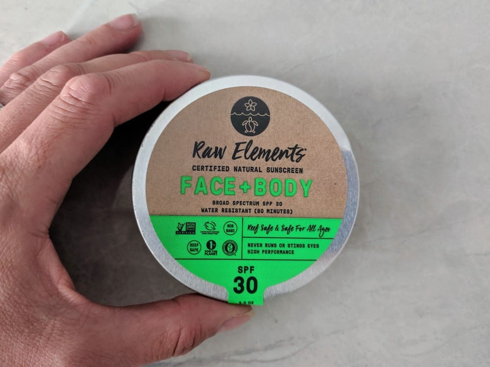 hand holding tin of Raw Elements sunscreen