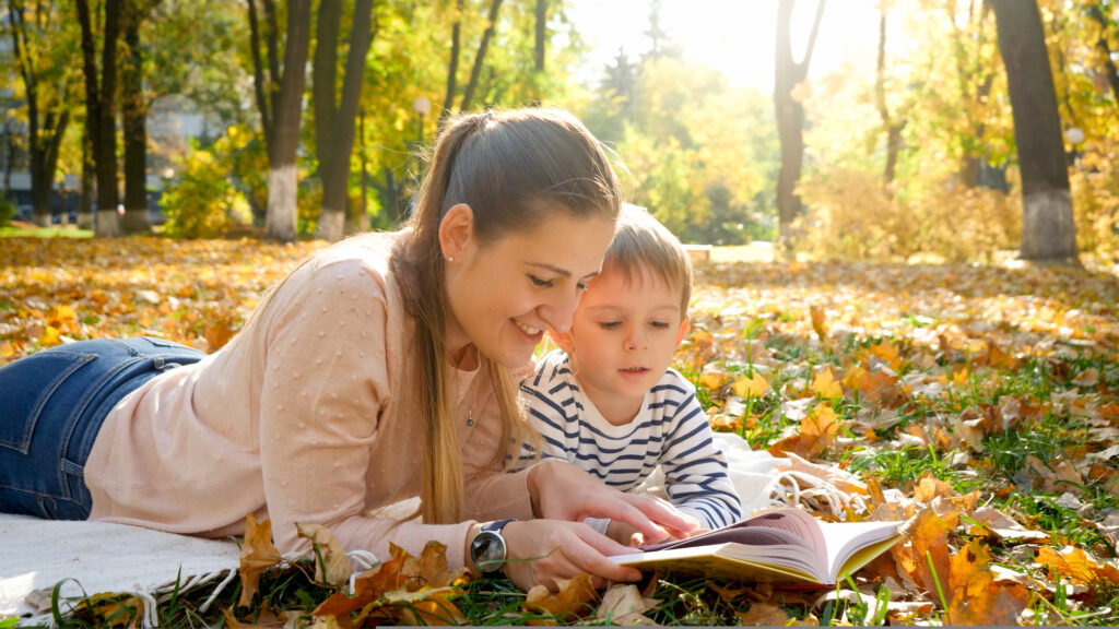Portrait of young mother telling a story to her little son lying on yellow fallen tree leaves at autumn park