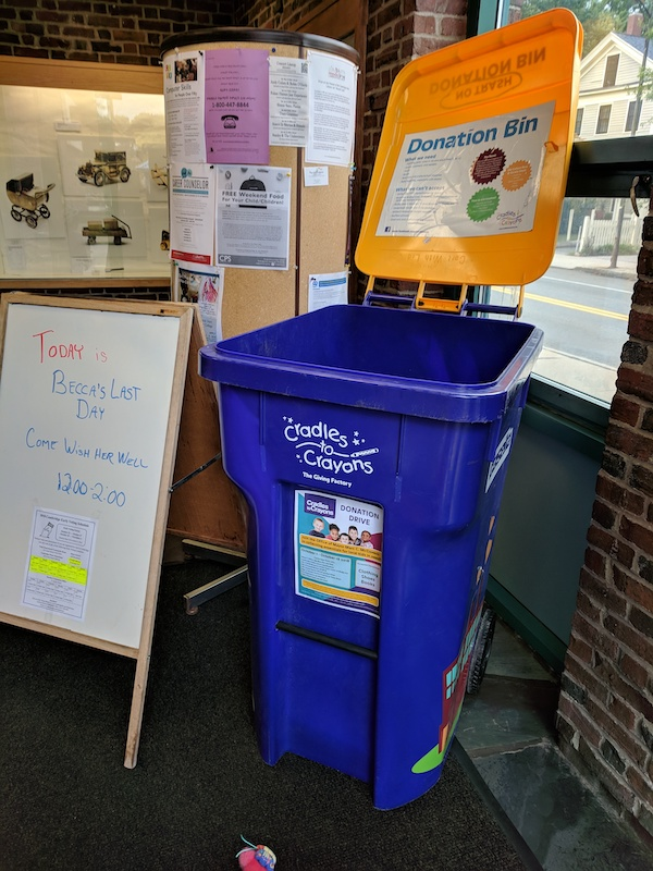Blue Cradles to Crayons donation bin in a library entryway