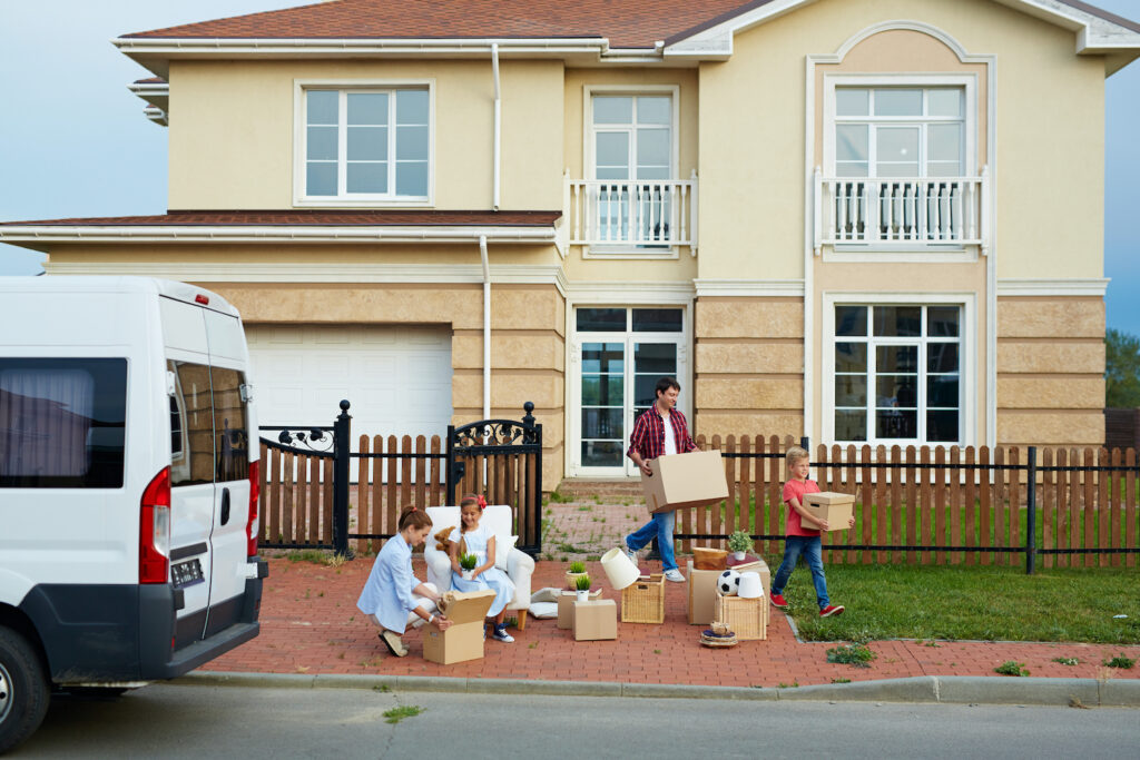 Portrait of family with two children moving out: mother and daughter busy sorting personal belongings in front of house while father and son taking out cardboard boxes to van outside